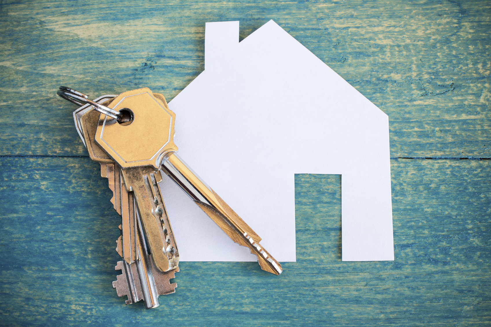 House icon and keys on wooden background