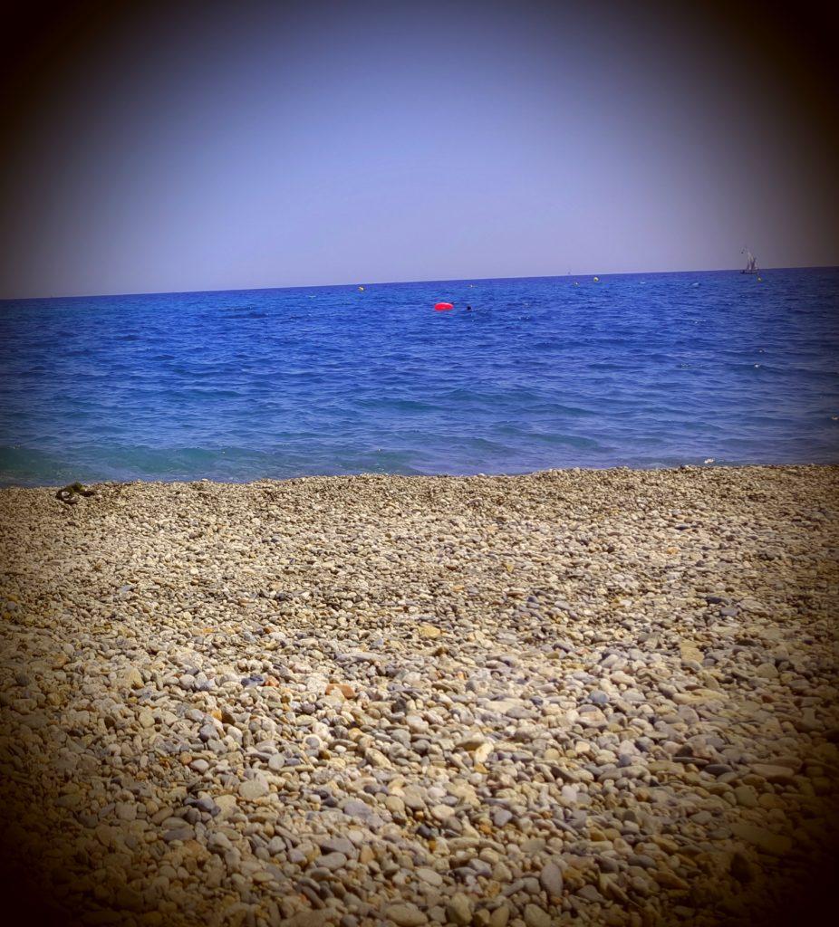 Stony beach with bright blue sea